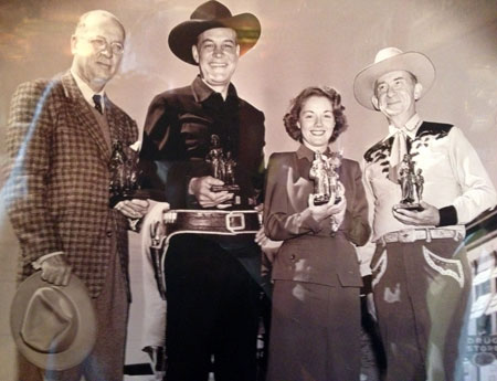 "In 1947 Columbia released Charles Starrett's ""Stranger from Ponca City"". This photo was taken when Starrett and others appeared in Ponca City, Oklahoma, for the screening of the film at the old Center Theatre. (L-R) Unknown, Starrett, leading lady Virginia Hunter and Roscoe Ates. It's odd Ates was there as he has no role in the film and wasn't really associated with Columbia Pictures. However, Smiley Burnette was there for the film but is not in this photo. Each of the four above are holding a scale model of the very famous Pioneer Woman statue which is in Ponca City. (www.okhistory.org/sites/pioneerwoman.php) Recently (10/18/15), I was in Ponca City, attended and spoke briefly before a special screening of ""Stranger from Ponca City"" at the Poncan Theatre along with Oklahoma Balladeer Les Gilliam and old friend Grant Hodges."