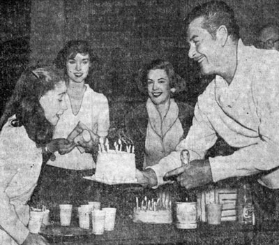 """Dodge City"", ""Rocky Mountain"", etc. Western star Errol Flynn presents a cake to Claudia Crawford on her 11th birthday in February '58. Looking on at the back stage party are Jan Brooks, Avis Scott. The company was getting ready to move to Detroit for the premiere of the play based on the novel JANE EYRE."