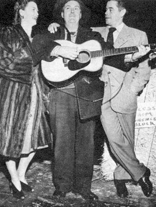Smiley Burnette serenades the Fords...Eleanor Powell and Glenn Ford at the Hitching Post Theatre in the Fall of '47.