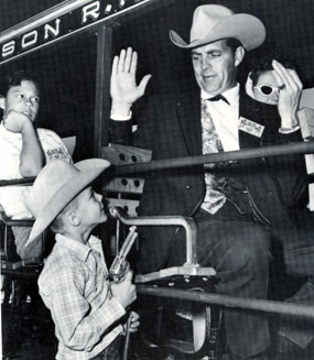 "Young George Masek of Tucson holds a gun on ""Tales of Wells Fargo"" star Dale Robertson at the official dedication of Old Tucson in January 1960."