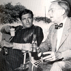 "TV's ""Wyatt Earp"", Hugh O'Brian, relaxes on the set with Stuart Lake, consultant to the ABC series, who knew the real Earp and gathered material for his book WYATT EARP, FRONTIER MARSHAL."