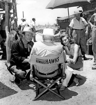 "John Wayne and Angie Dickinson listen to director Howard Hawks on the set of ""Rio Bravo"" ('59 Warner Bros.)."