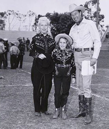 Western tailor Nudie's wife Bobbie and daughter Barbara pose with Bill Elliott.
