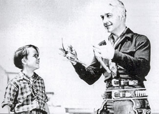 "Willliam Boyd (Hopalong Cassidy) impresses young Dickie Jones with some fancy gun handling during the making of ""The Frontiersman"" ('38 Paramount)."