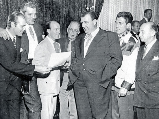 "Reshearsing a song for a charity affair are Allan ""Rocky"" Lane (sans hairpiece), Buddy Baer, Tim Spencer, Hoot Gibson, Andy Devine, Ken Curtis and Roscoe Ates."