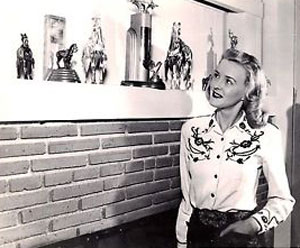 Rodeo queen and Monogram B-Western leading lady Reno Browne looks at some of her many rodeo trophies.