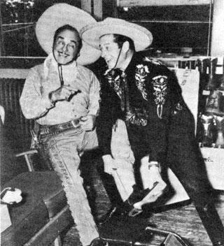 The Cisco Kid (Duncan Renaldo) fits sidekick Pancho (Leo Carrillo) with a pair of boots at the H. J. Justin and Sons plant's 75th Anniversary in Fort Worth, Texas.