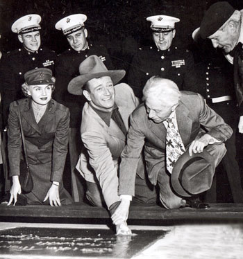 Sid Grauman helps John Wayne put his fist and boot prints into the cement outside Grauman's Chinese Theater on January 25, 1950. Wayne's concrete block is made from black cement from the black sands of Iwo Jima.
