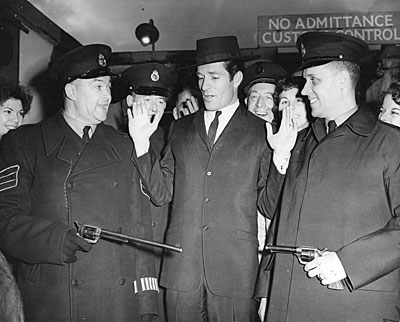 "Hugh ""Wyatt Earp"" O'Brian, arriving at Heathrow Airport in 1958, is disarmed of his Buntline Special and sixgun by London Customs officials. (Thanx to Terry Cutts.)"