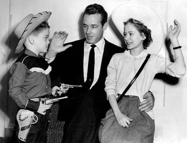 "Sixguns in hand, five year old Dickie Barrett aims to get Wild Bill Hickok's contribution to the Heart Fund while Guy Madison was filming ""The Command"" in 1954."