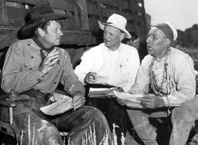 "On location for ""The Outriders"", Joel McCrea goes over some script pages with script supervisor Don McDougal and Nipo T. Strongheart."
