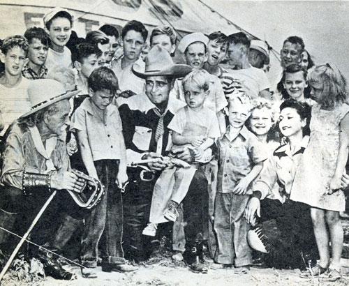 Silent and early '30s B-Western star Jack Hoxie surrounded by a group of admiring fans.