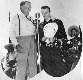 Oklahoma Governor Robert S. Kerr and Jimmy Wakely sing a duet and do a little kidding at the dedication ceremonies of a Chisholm Trail marker in Enid, Oklahoma in the mid '40s. Kerr was Governor from '43 to '47.