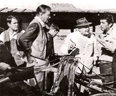 "Director Henry Hathaway talks over a scene for ""The Sons of Katie Elder"" with Earl Holliman, John Wayne and Dean Martin."