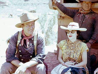 "John Wayne and his wife Pilar relax on location during the filming of ""The Searchers"" ('56). They were married in '54."