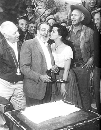"Frank McGrath, Charlie Wooster on ""Wagon Train"", celebrates his 58th birthday on February 2, 1961 while filming the ""Tiburcio Mendez Story"" and receives a kiss from guest star Lisa Gaye. Terry Wilson in on the right. Cinematographer Walter Stenge is on the left."