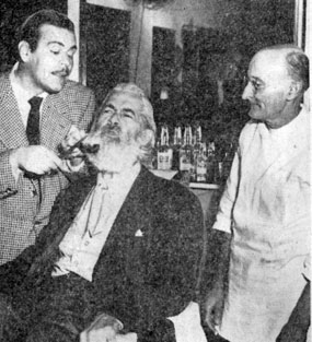"Gabby Hayes gets his beard trimmed by comedian Billy De Wolff while barber R. D. Carothers supervises. The stars were at the Southern Pacific terminal in Houston for the opening there of ""Albuquerque"" on 2/4/48."