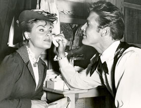 "Roger Moore helps to touch up Kathleen Crowley's make-up as they prepare for a scene on ""Maverick: A Bullet for the Teacher""."