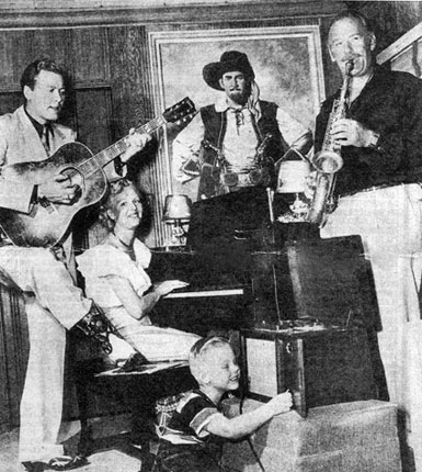 "Roy Barcroft on saxophone, Monte Hale on guitar, Roy's wife on piano with young Michael Barcroft recording the jam session in Barcroft's home. Note the painting of Barcroft as Captain Mephisto used in the 1945 Republic serial ""Manhunt of Mystery Island"". (Photo courtesy Bob Burns and CI.)"