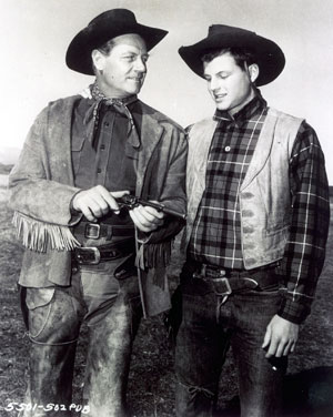 "Joel McCrea demonstrates the finer points of his six-shooter to son Jody while filming ""Wichita"" ('55)."