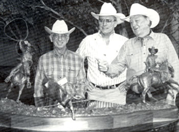 Team roper Joe Crow (left) and his favorite roping partner Ben Johnson (right) flank sculptor Edd Hayes at a Ben Johnson/Bum Phillips Celebrity Roping and Cutting in Houston, Texas. Hayes created the 110 lb. bronze which sold for $62,000 at auction.