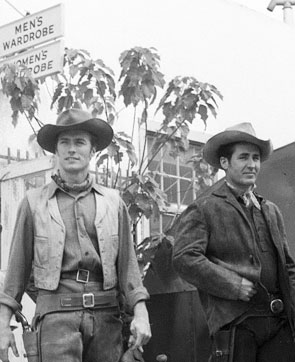 "Clint Eastwood and Sheb Wooley emerge from men›s wardrobe ready for action on another episode of ""Rawhide"". (Thanx to Terry Cutts.)"