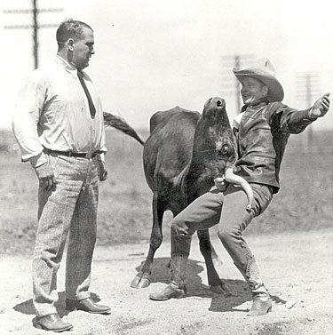 "World Champion cowboy Yakima Canutt shows four time World Heavyweight Championship Wrestler Ed ""Strangler"" Lewis how to hold ‹em with one hand. Photo circa late '20s-very early '30s."