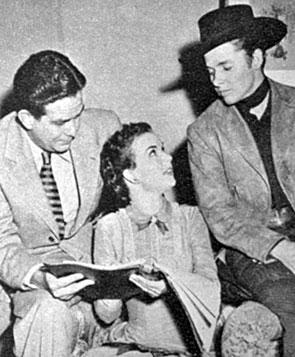 "Gale Storm looks over the script for ""The Kid From Texas' ('50) with producer Paul Short and star Audie Murphy."