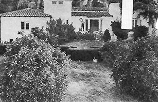 Roy Rogers waves from the front porch of his San Fernando Valley home circa 1942. Property had a swimming pool, tennis court, guest house, citrus orchard and huge corral.