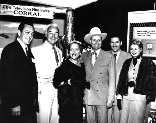 "Publicity photo for syndication of various TV shows in the mid '50s. (L-R) Don Haggerty (""Cases of Eddie Drake""/""Cases of Jeffrey Jones""), William Boyd (""Hopalong Cassidy""), Gloria Swanson (""Gloria Swanson Presents""), Gene Autry and Pat Buttram (""The Gene Autry Show""), Gail Davis (""Annie Oakley""). Note the ""Range Rider"" promo on the wall. (Photo courtesy Dale Price.)"