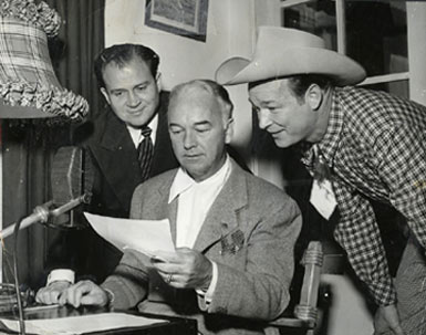 "Noted Los Angeles radio disc jockey Al Jarvis (""Make Believe Ballroom"") rehearses with William (Hopalong Cassidy) Boyd and Roy Rogers. Jarvis also had a five hour a day TV talk show on KLAC-TV in the '50s ."