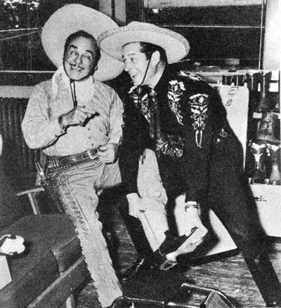 Duncan Renaldo, the Cisco Kid, fits his pal Leo Carrillo, Pancho, with a pair of boots at the Justin Boot plant in Fort Worth, TX, during the company's 75th anniversary in 1954.