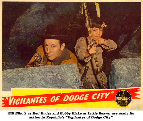 "Bill Elliott as Red Ryder and Bobby Blake as Little Beaver are ready for action in Republic's ""Vigilantes of Dodge City""."