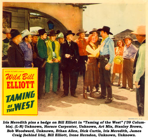 "Iris Meredith pins a badge on Bill Elliott in ""Taming of the West"" ('39 Columbia). (L-R) Unknown, Horace Carpenter, Unknown, Art Mix, Stanley Brown, Bob Woodward, Unknown, Ethan Allen, Dick Curtis, Iris Meredith, James Craig (behind Iris), Bill Elliott, Irene Herndon, Unknown, Unknown."
