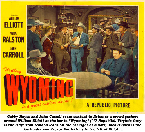 "Gabby Hayes and John Carroll seem content to listen as a crowd gathers around William Elliott at the bar in ""Wyoming"" ('47 Republic). Virginian Grey is the lady; Tom London leans on the bar right of Elliott; Jack O'Shea is the bartneder and Trevor Bardette is to the left of Elliott."