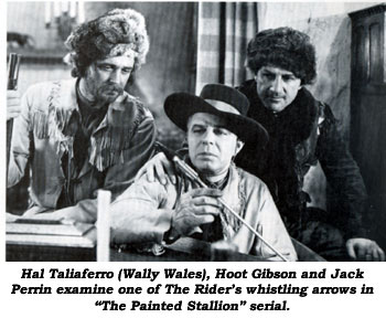"Hal Taliaferro (Wally Wales), Hoot Gibson and Jack Perrin examine one of The Rider's whistling arrows in ""The Painted Stallion"" serial."