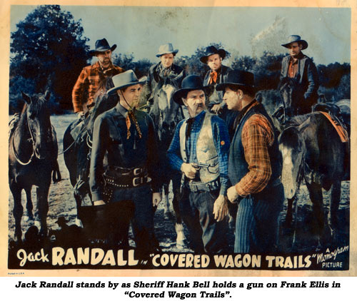 "Jack Randall stands by as Sheriff Hank Bell holds a gun on Frank Ellis in ""Covered Wagon Trails""."