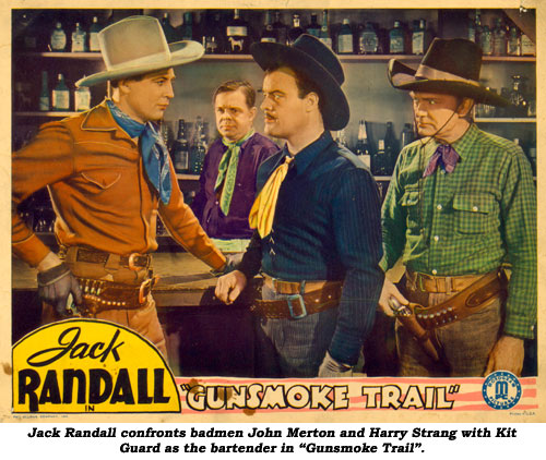 "Jack Randall confronts John Merton and Harry Strang with Kit Guard as bartender in ""Gunsmoke Trail""."